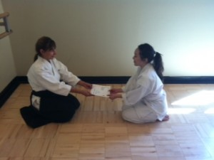 Instructor Kara Stewart presents Katie-san with 6th kyu certificate.